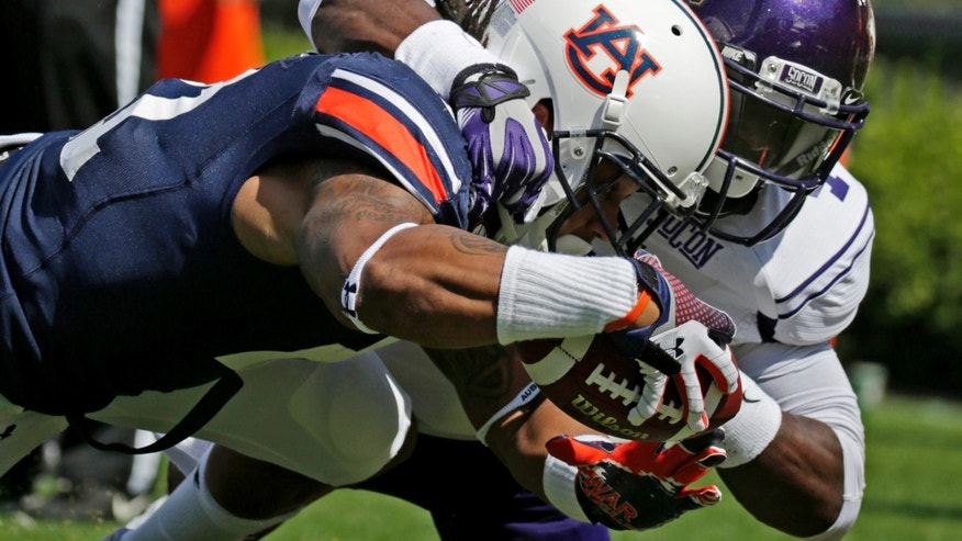 Auburn running back Tre Mason (21) dives into the end zone to score as Western Carolina defensive back Sertonuse Harris (4) defends in the first half of an NCAA college football game in Auburn, Ala., Saturday, Oct. 12, 2013. (AP Photo/Dave Martin)