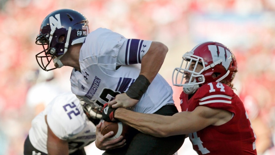 Northwestern quarterback Trevor Siemian is sacked by Wisconsin safety Nate Hammon during the first half of an NCAA college football game in Madison, Wis., Saturday, Oct. 12, 2013. (AP Photo/Andy Manis)