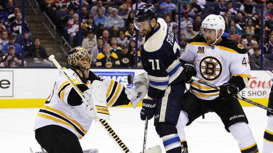 Boston Bruins' Tuukka Rask, left, of Finland, makes a save as teammate Dennis Seidenberg, right, of Germany and Columbus Blue Jackets' Nick Foligno wait for the rebound during the second period of an NHL hockey game Saturday, Oct. 12, 2013, in Columbus, Ohio. (AP Photo/Jay LaPrete)