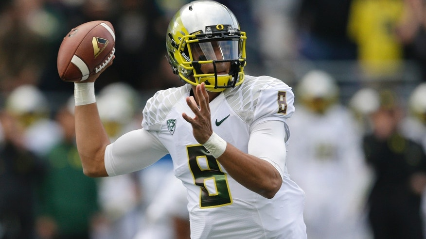 Oregon quarterback Marcus Mariota passes against Washington in the first half of an NCAA college football game, Saturday, Oct. 12, 2013, in Seattle. (AP Photo/Ted S. Warren)
