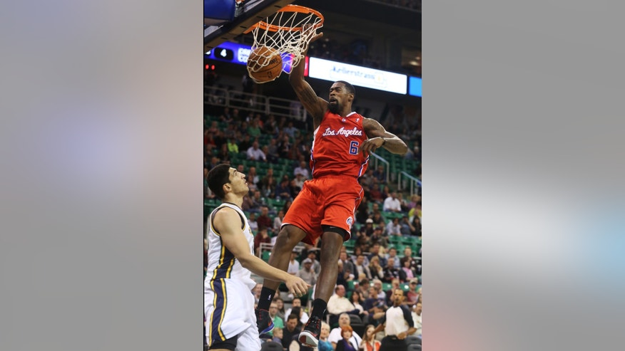 Los Angeles Clippers' DeAndre Jordan (6) dunks the ball over Utah Jazz's Enes Kanter (0) in the first quarter during an NBA preseason basketball game on Saturday, Oct. 12, 2013, in Salt Lake City. (AP Photo/Kim Raff)