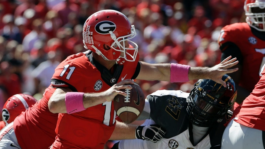 Georgia quarterback Aaron Murray throws under pressure from Missouri's Kony Ealy during the second half of an NCAA college football game Saturday, Oct. 12, 2013, in Athens, Ga. Missouri won 41-26. (AP Photo/John Bazemore)