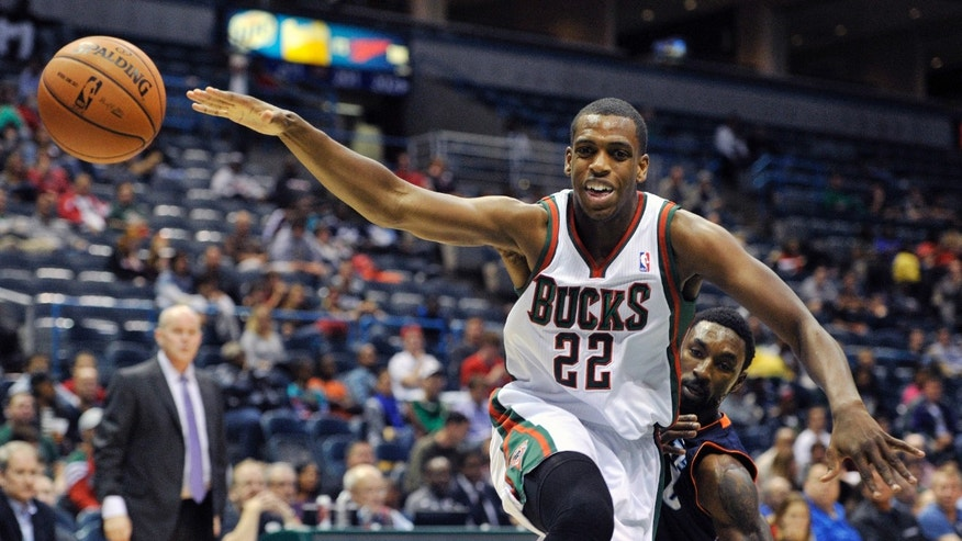 Milwaukee Bucks' Khris Middleton (22) looses the ball as the Charlotte Bobcats' Ben Gordon defends during the second half of an NBA basketball game Saturday, Oct. 12, 2013, in Milwaukee. The Bobcats defeated the Bucks 83-76. (AP Photo/Jim Prisching)