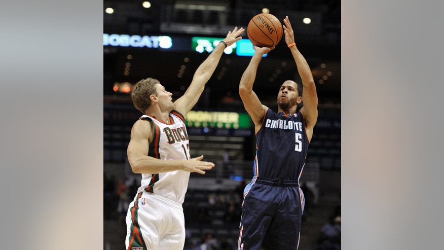 Milwaukee Bucks' Luke Ridnour tries to block the shot of the Charlotte Bobcats' Jannero Pargo (5) during the first half of an NBA basketball game Saturday, Oct. 12, 2013, in Milwaukee. (AP Photo/Jim Prisching)