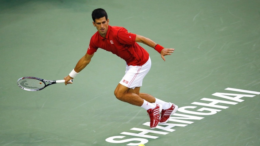 Serbia's Novak Djokovic returns a shot to France's Jo-Wilfried Tsonga during the singles semifinal match of the Shanghai Masters tennis tournament at Qizhong Forest Sports City Tennis Center in Shanghai, China, Saturday, Oct. 12, 2013. (AP Photo/Eugene Hoshiko)