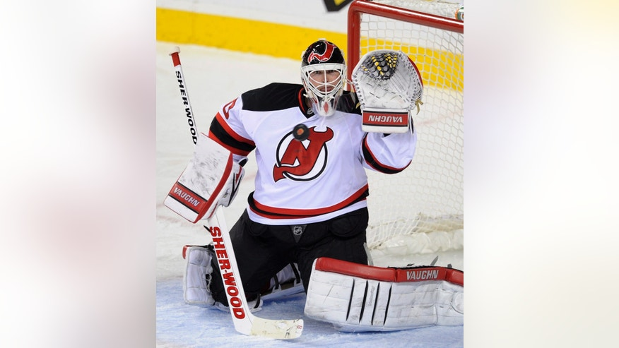 New Jersey Devils goalie Martin Brodeur makes a save on a Calgary Flames shot during the third period of an NHL hockey game Friday, Oct. 11, 2013, in Calgary, Alberta. The Flames won 3-2. (AP Photo/The Canadian Press, Larry MacDougal)