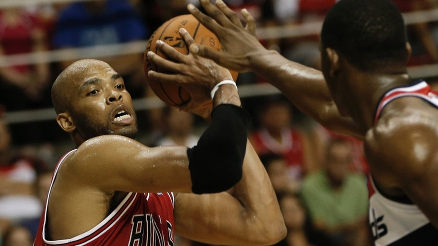 Chicago Bulls' Taj Gibson is blocked by Washington Wizards' Kevin Seraphin during the first half of an NBA preseason basketball game in Rio de Janeiro, Brazil, Saturday, Oct. 12, 2013. (AP Photo/Felipe Dana)