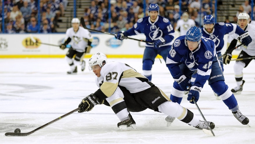 Pittsburgh Penguins center Sidney Crosby (87) is tripped by Tampa Bay Lightning left wing Ondrej Palat (18), of the Czech Republic, during the first period of an NHL hockey game on Saturday, Oct. 12, 2013, in Tampa, Fla. (AP Photo/Chris O'Meara)