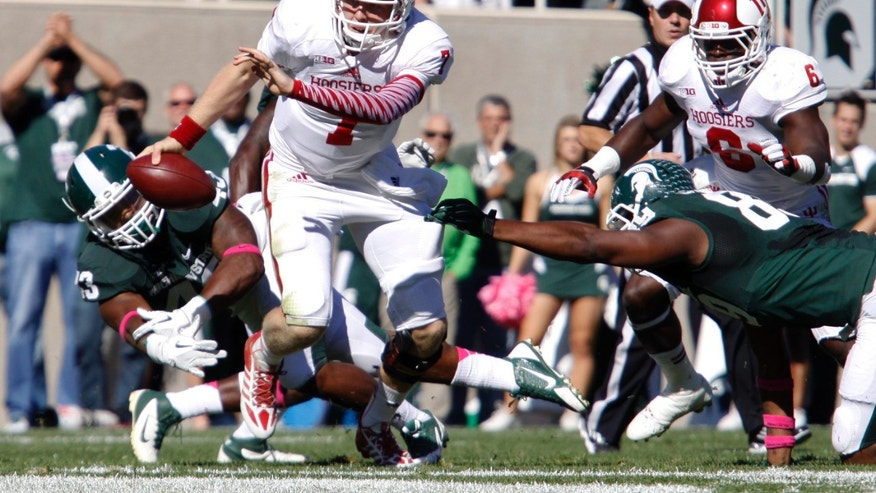 Indiana quarterback Nate Sudfeld, center, escapes from Michigan State's Shilique Calhoun, right, and Ed Davis on a keeper during the first quarter of an NCAA college football game, Saturday, Oct. 12, 2013, in East Lansing, Mich. At right rear is Indiana's Tevin Coleman (6) (AP Photo/Al Goldis)