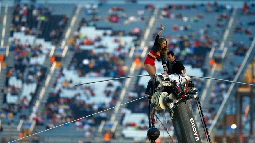 Lijana Wallenda waves after completing a walk walks across the tightrope before the NASCAR Sprint Cup Series auto race at Charlotte Motor Speedway in Concord, N.C., Saturday, Oct. 12, 2013. (AP Photo/Chris Keane)