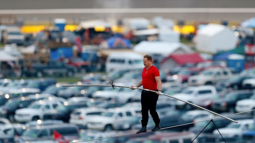 Nik Wallenda walks across the tightrope before the NASCAR Sprint Cup Series auto race at Charlotte Motor Speedway in Concord, N.C., Saturday, Oct. 12, 2013. (AP Photo/Chris Keane)