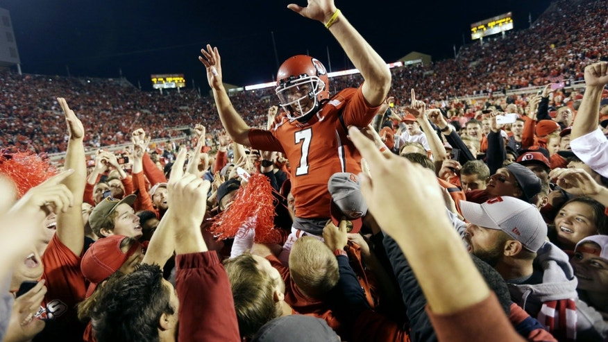Utah quarterback Travis Wilson (7) is hoisted to the air by Utah fans after defeating Stanford 27-21 during an NCAA college football game on Saturday, Oct. 12, 2013, in Salt Lake City. (AP Photo/Rick Bowmer)