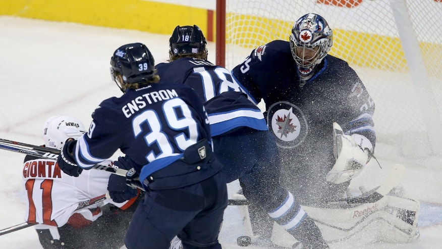New Jersey Devils' Stephen Gionta (11) slides in front of the Winnipeg Jets net as Toby Enstrom (39), Bryan Little (18) and goaltender Al Montoya (35) try to stop the puck during first period of an NHL hockey game in Winnipeg, Manitoba, on Sunday, Oct. 13, 2013. (AP Photo/The Canadian Press, Trevor Hagan)