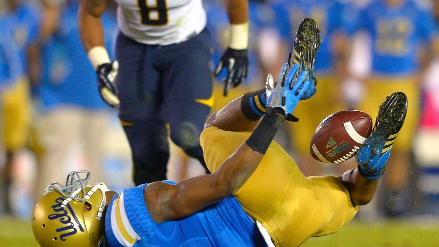 UCLA wide receiver Shaquelle Evans, below, traps a pass between his legs as California linebacker Michael Barton looks on during the first half of their NCAA college football game, Saturday, Oct. 12, 2013, in Pasadena, Calif. (AP Photo/Mark J. Terrill)