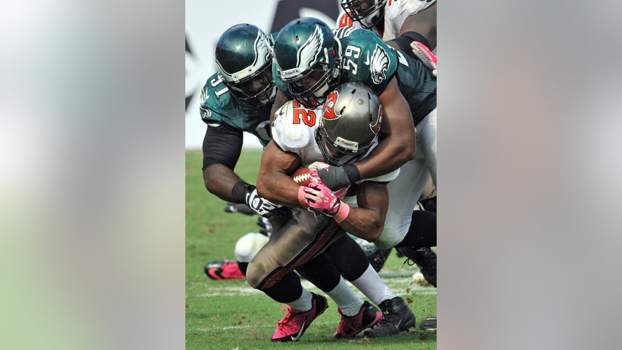 Tampa Bay Buccaneers running back Doug Martin (22) is stopped by Philadelphia Eagles inside linebacker DeMeco Ryans (59) and defensive end Fletcher Cox (91) during the fourth quarter of an NFL football game Sunday, Oct. 13, 2013, in Tampa, Fla. (AP Photo/Steve Nesius)
