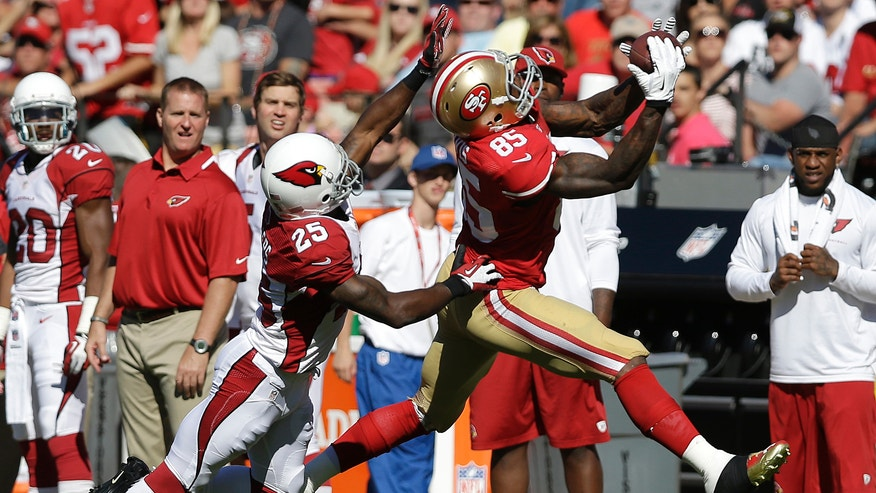 San Francisco 49ers tight end Vernon Davis (85) catches a pass over Arizona Cardinals cornerback Jerraud Powers (25) during the second quarter of an NFL football game in San Francisco, Sunday, Oct. 13, 2013. (AP Photo/Marcio Jose Sanchez)