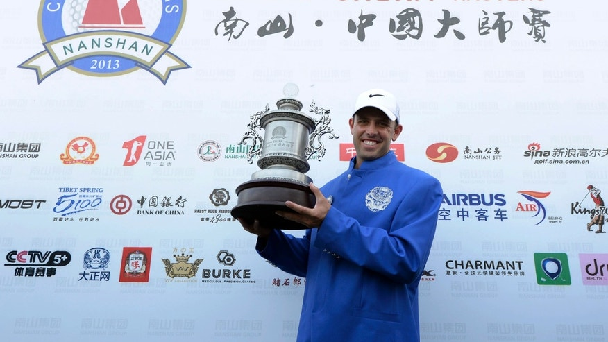 In this photo released by OneAsia, Charl Schwartzel of South Africa poses with the winner's trophy after the final round of the Nanshan China Masters golf tournament at the Nanshan International Golf Club in Longkou, Shandong Province, China Sunday, Oct. 13, 2013. (AP Photo/OneAsia, Paul Lakatos) NO LICENSING