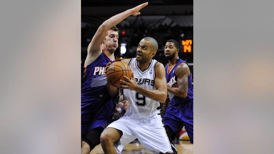 San Antonio Spurs' Tony Parker (9), of France, drives around Phoenix Suns' Goran Dragic, of Slovenia, during the first half of an NBA preseason basketball game on Sunday, Oct. 13, 2013, in San Antonio. (AP Photo/Darren Abate)