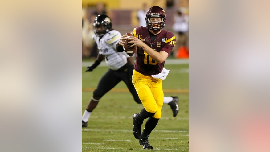 Arizona States' Taylor Kelly, right, eludes Colorado's Derrick Webb, left, as he runs with the ball during the first half of an NCAA college football game on Saturday Oct. 12, 2013, in Tempe, Ariz. (AP Photo/Ross D. Franklin)