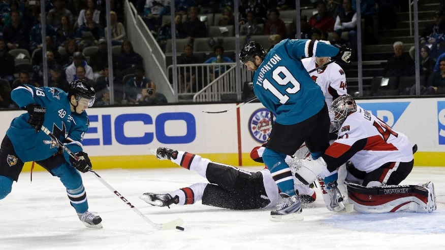 San Jose Sharks' Tomas Hertl, left, of the Czech Republic, controls the puck next to teammate Joe Thornton (19) and Ottawa Senators goalie Robin Lehner during the first period of an NHL hockey game Saturday, Oct. 12, 2013, in San Jose, Calif. (AP Photo/Marcio Jose Sanchez)