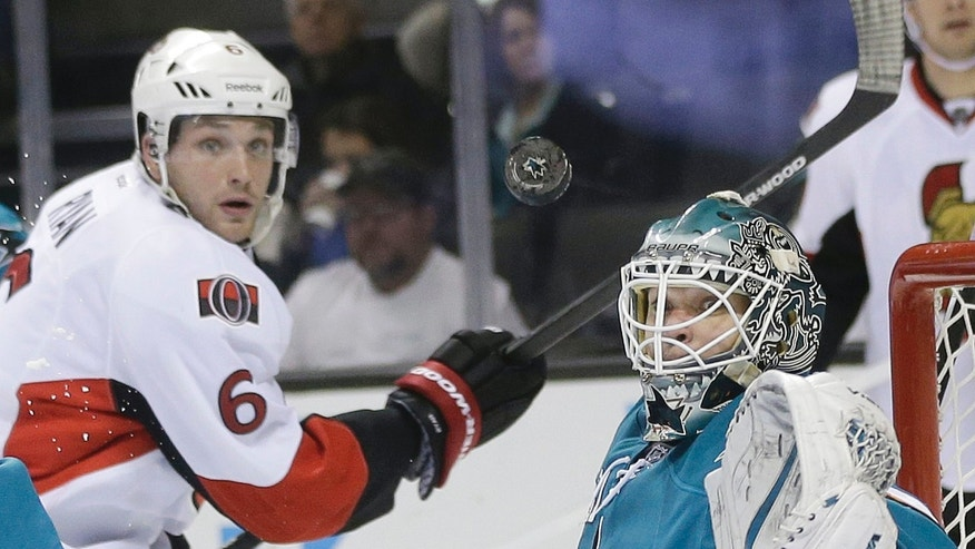 San Jose Sharks goalie Antti Niemi, of Finland, right stops a shot next to Ottawa Senators' Bobby Ryan (6) during the second period of an NHL hockey game Saturday, Oct. 12, 2013, in San Jose, Calif. (AP Photo/Marcio Jose Sanchez)