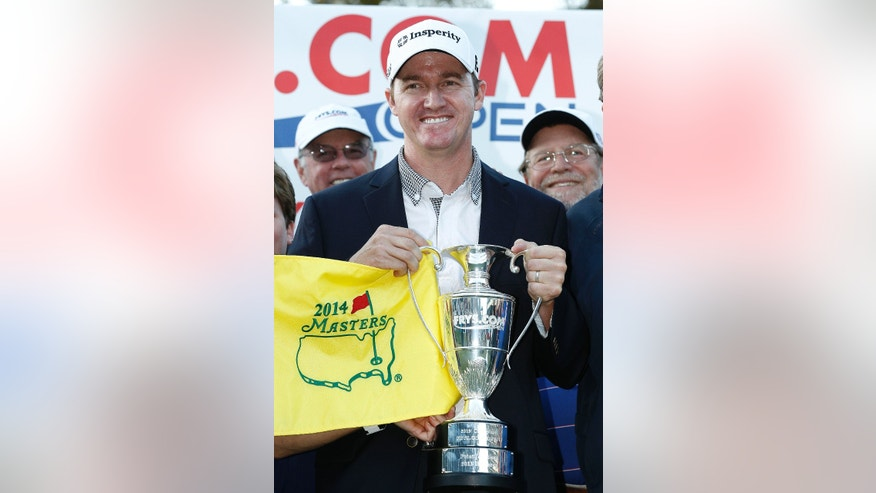 Jimmy Walker holds the trophy and a Masters flag after winning the Frys.com Open golf tournament, Sunday, Oct. 13, 2013, in San Martin, Calif. (AP Photo/Tony Avelar)