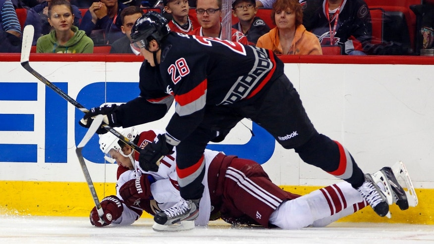 Carolina Hurricanes' Alexander Semin (28) of Russia, collides with Phoenix Coyotes' Martin Hanzal (11) of Czech Republic,  during the second period of an NHL hockey game, Sunday, Oct. 13, 2013, in Raleigh, N.C. (AP Photo/Karl B DeBlaker)
