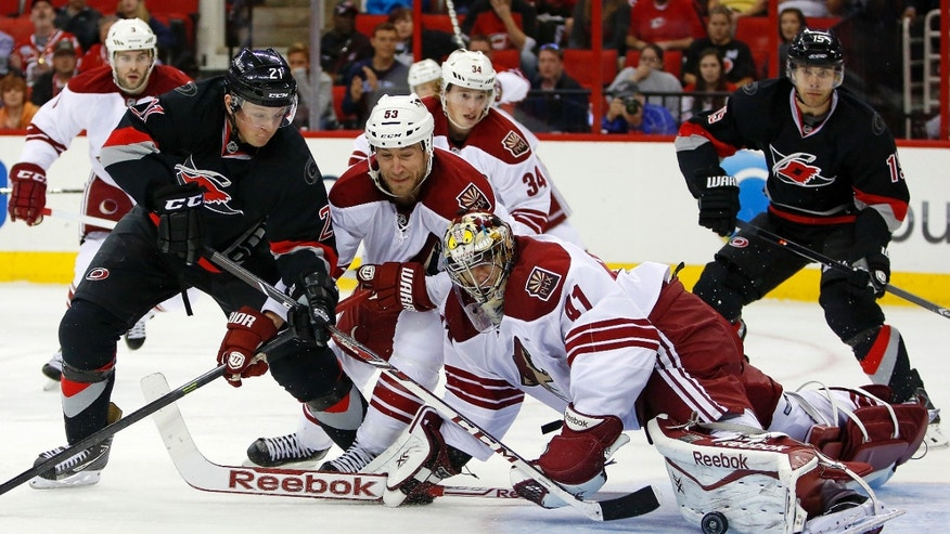 Carolina Hurricanes' Drayson Bowman (21) has his shot blocked by Phoenix Coyotes goalie Mike Smith (41) and Derek Morris (53) with Hurricanes' Tuomo Ruutu (15), of Finland, watching at right during the second period of an NHL hockey game, Sunday, Oct. 13, 2013, in Raleigh, N.C. (AP Photo/Karl B DeBlaker)