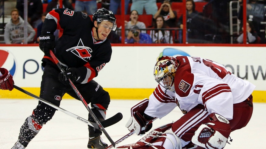 Phoenix Coyotes goalie Mike Smith (41) kicks the shot of Carolina Hurricanes' Jeff Skinner (53) away from the net during the second period of an NHL hockey game, Sunday, Oct. 13, 2013, in Raleigh, N.C. (AP Photo/Karl B DeBlaker)