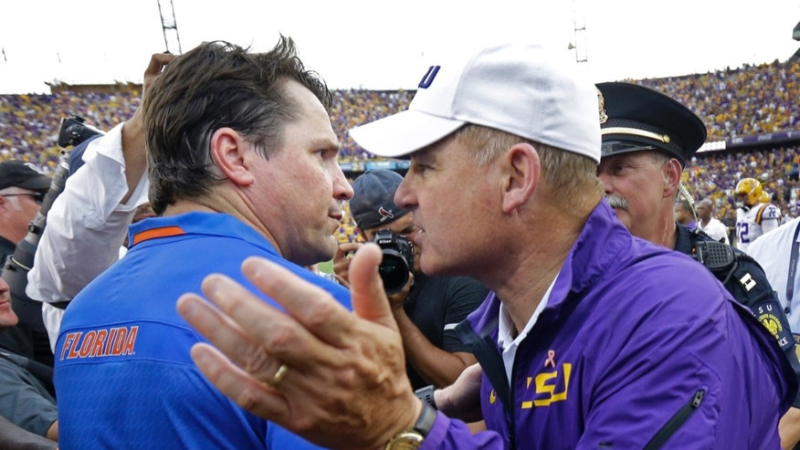 LSU head coach Les Miles, right, greets Florida head coach Will Muschamp after an NCAA college football game in Baton Rouge, La., Saturday, Oct. 12, 2013.  LSU won 17-6. (AP Photo/Gerald Herbert)