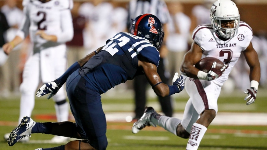 Texas A&M running back Trey Williams (3) runs past Mississippi defensive back Tony Conner (12) for short yards in the second half of their NCAA college football game at Vaught-Hemingway Stadium in Oxford, Miss., Saturday, Oct. 12, 2013. No. 9 Texas A&M won 41-38. (AP Photo/Rogelio V. Solis)