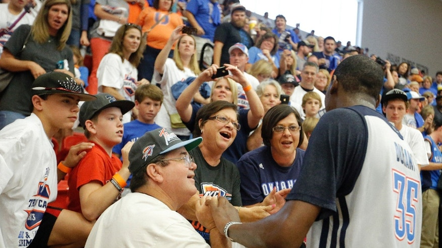 Oklahoma City NBA basketball team's Kevin Durant (35) greets fans following the their Blue and White scrimmage at Westmoore High School in Moore, Okla., Sunday, Oct. 13, 2013. (AP Photo/The Oklahoman, Sarah Phipps)
