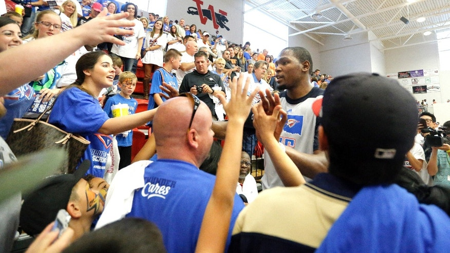 Oklahoma City Thunder NBA basketball player Kevin Durant (35) greets fans following the Thunder's  Blue and White scrimmage at Westmoore High School in Moore, Okla., Sunday, Oct. 13, 2013. (AP Photo/The Oklahoman, Sarah Phipps)