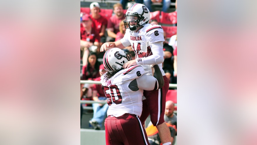 South Carolina left guard A.J. Cann (50) lifts Connor Shaw (14) after Shaw scored during the second half of an NCAA college football game against Arkansas in Fayetteville, Ark., Saturday, Oct. 12, 2013. South Carolina won 52-7. (AP Photo/April L Brown)
