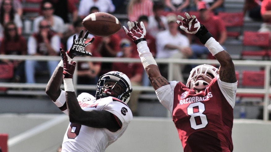 Arkansas cornerback Tevin Mitchel (8) deflects a pass intended for South Carolina wide receiver Shamier Jeffery during the second half of an NCAA college football game in Fayetteville, Ark., Saturday, Oct. 12, 2013. South Carolina defeated Arkansas 52-7. (AP Photo/April L Brown)
