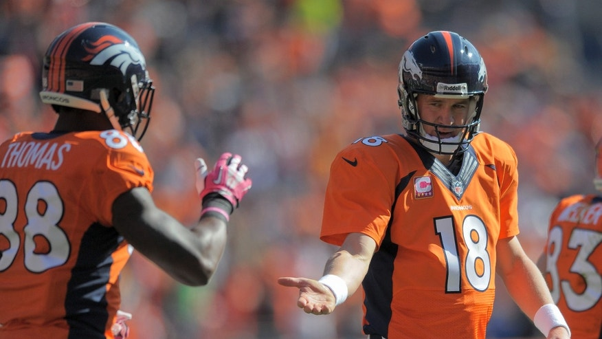Denver Broncos quarterback Peyton Manning (18) reaches for a hand from wide receiver Demaryius Thomas (88) after a Denver touchdown against the Jacksonville Jaguars in the first quarter of an NFL football game, Sunday, Oct. 13, 2013, in Denver. (AP Photo/Jack Dempsey)