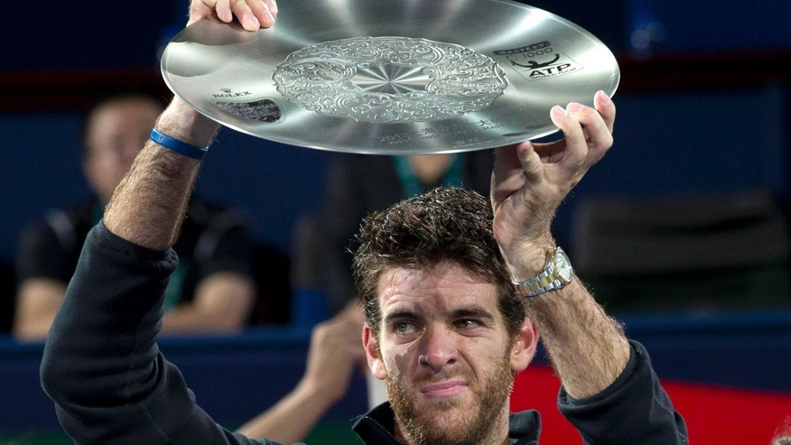 Argentina's Juan Martin del Potro raises his trophy after losing to Serbia's Novak Djokovic 6-1, 3-6, 7-6 (3) in their final match at the Shanghai Masters tennis tournament at the Qizhong Forest Sports City Tennis Center in Shanghai, China, Sunday, Oct. 13, 2013. (AP Photo/Ng Han Guan)