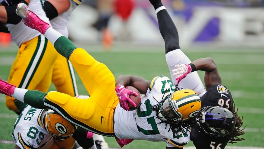 Green Bay Packers running back Eddie Lacy (27) is knocked off his feet by Baltimore Ravens inside linebacker Josh Bynes (56) during the first half of an NFL football game in Baltimore, Sunday, Oct. 13, 2013. (AP Photo/Nick Wass)