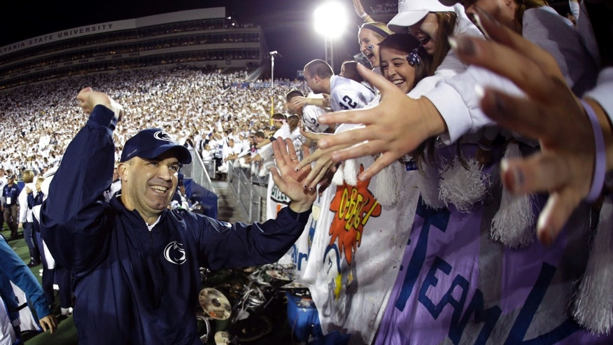 In this image made with a fisheye lens, Penn State head coach Bill O' Brien celebrates with students after a 43-40 win over Michigan during an NCAA college football game in State College, Pa., Saturday, Oct. 12, 2013.  (AP Photo/Gene J. Puskar)
