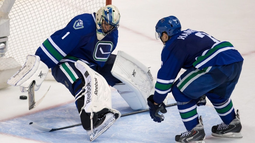 Vancouver Canucks' Dan Hamhuis, right, and goalie Roberto Luongo watch as a Canucks pass bounces off Luongo's skate and into their own net for a Montreal Canadiens goal during the second period of an NHL hockey game in Vancouver, British Columbia, on Saturday, Oct. 12, 2013. (AP Photo/The Canadian Press, Darryl Dyck)