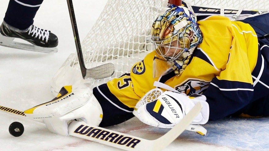 Nashville Predators goalie Pekka Rinne, of Finland, blocks a shot against the New York Islanders in the first period of an NHL hockey game on Saturday, Oct. 12, 2013, in Nashville, Tenn. (AP Photo/Mark Humphrey)