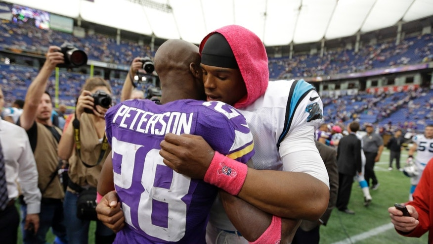 Minnesota Vikings running back Adrian Peterson, left, hugs Carolina Panthers quarterback Cam Newton following a 35-10 Panthers win in an NFL football game in Minneapolis, Sunday, Oct. 13, 2013. One of Peterson's sons, a 2-year-old in South Dakota, died Friday after an alleged attack in a child abuse case. (AP Photo/Michael Conroy)