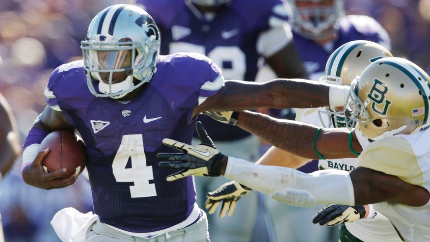 Kansas State quarterback Daniel Sams (4) stiff-arms his way past Baylor safety Ahmad Dixon, right, during the first half of an NCAA college football game in Manhattan, Kan., Saturday, Oct. 12, 2013. (AP Photo/Orlin Wagner)