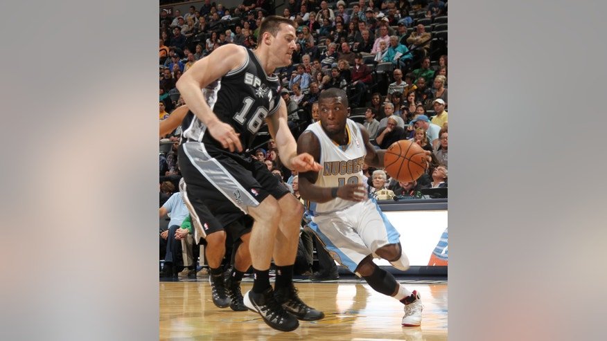 Denver Nuggets guard Nate Robinson, right, works ball inside as San Antonio Spurs forward Aron Baynes covers in the first quarter of an NBA preseason basketball game in Denver on Monday, Oct. 14, 2013. (AP Photo/David Zalubowski)