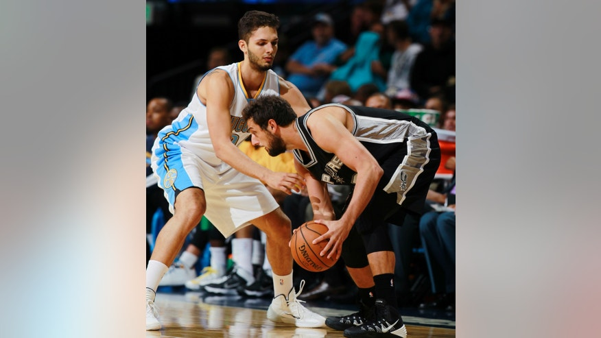 San Antonio Spurs guard Marco Belinelli, right, of Italy, works ball inside against Denver Nuggets guard Evan Fournier, of France, in the first quarter of an NBA preseason basketball game in Denver on Monday, Oct. 14, 2013. (AP Photo/David Zalubowski)