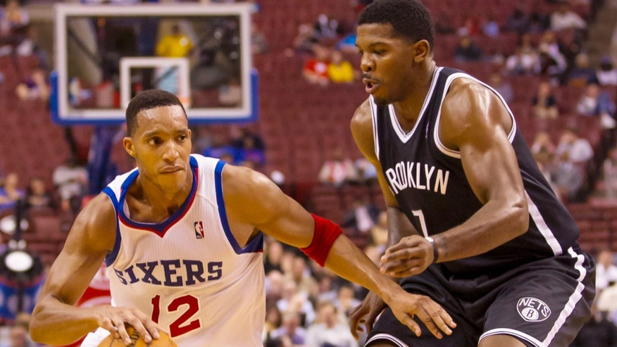 Philadelphia 76ers' Evan Turner, left, drives to the basket with Brooklyn Nets' Joe Johnson, right, defending him during the second quarter of a preseason NBA basketball game, Monday, Oct. 14, 2013, in Philadelphia.  (AP Photo/Chris Szagola)