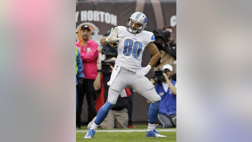 Detroit Lions tight end Joseph Fauria (80) celebrates his 1-yard touchdown catch against the Cleveland Browns in the first quarter of an NFL football game Sunday, Oct. 13, 2013, in Cleveland. (AP Photo/Tony Dejak)