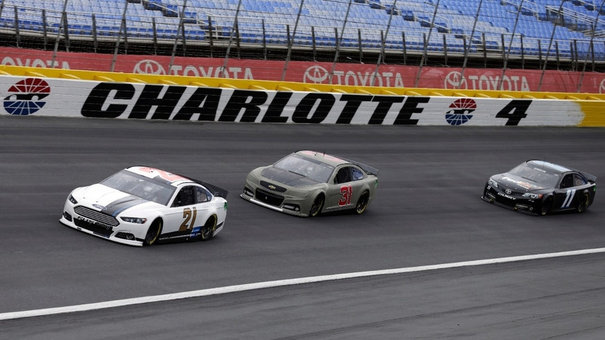 Drivers, from left, Trevor Bayne, Jeff Burton, and Denny Hamlin race through Turn 4 during a testing session for NASCAR Sprint Cup series auto race cars at Charlotte Motor Speedway in Concord, N.C., Monday, Oct. 14, 2013. (AP Photo/Chuck Burton)