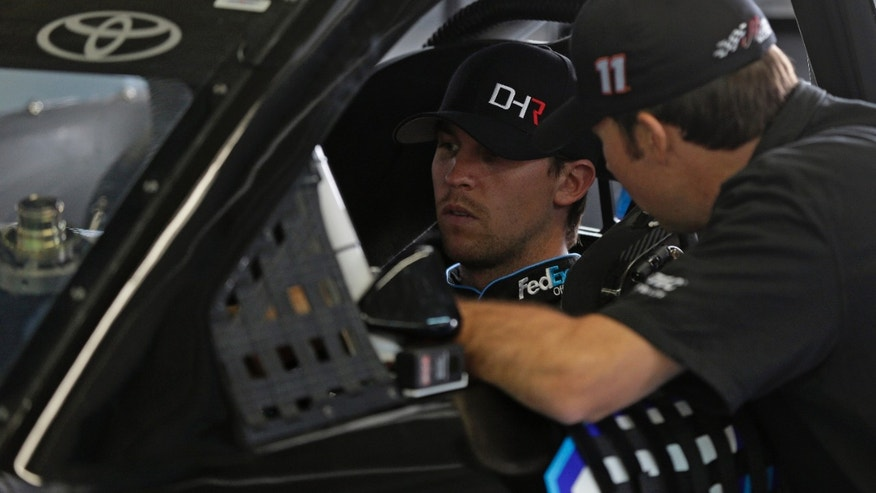 Driver Denny Hamlin, left, talks to a crew member during a testing session for NASCAR Sprint Cup series auto race cars at Charlotte Motor Speedway in Concord, N.C., Monday, Oct. 14, 2013. (AP Photo/Chuck Burton)