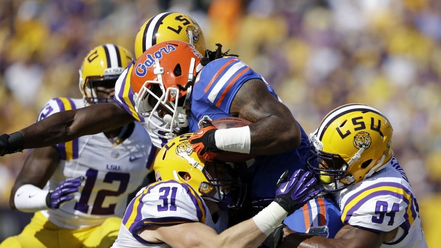 Florida running back Matt Jones is tackled by LSU linebacker D.J. Welter (31) and defensive end Danielle Hunter (94)in the first half of an NCAA college football game in Baton Rouge, La., Saturday, Oct. 12, 2013. (AP Photo/Gerald Herbert)